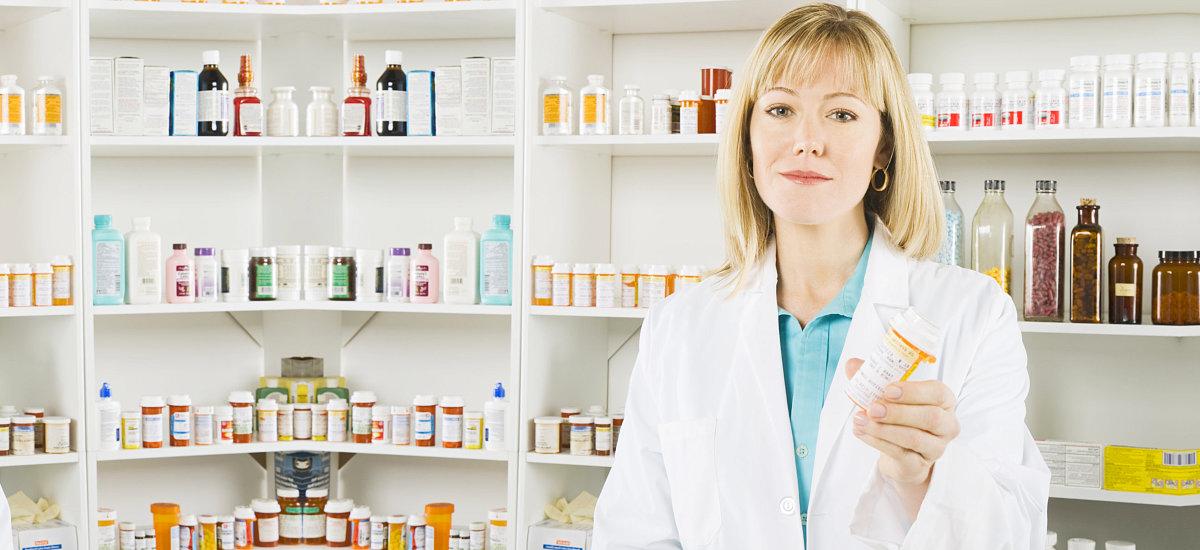 female pharmacist holding medicine bottle