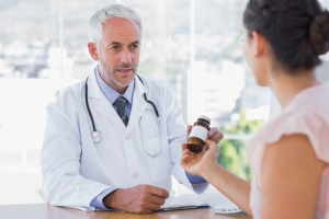 patient holding a bottle of medicine talking to a pharmacist